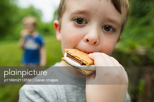 Portrait of boy eating smore with brother while standing in backyard - p1166m2112550 by Cavan Images