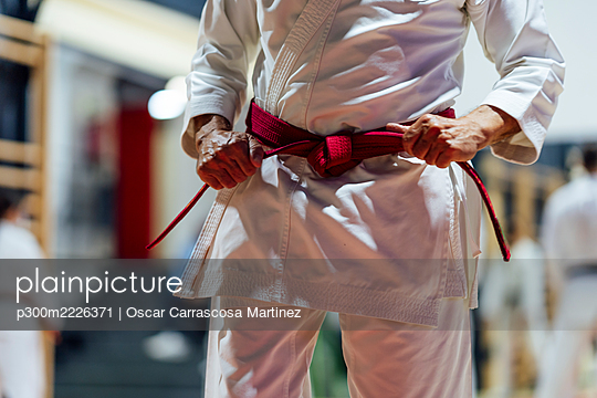 Active senior man tightening belt while practicing karate in class - p300m2226371 by Oscar Carrascosa Martinez