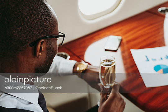 Young businessman with champagne traveling in airplane - p300m2257087 by OneInchPunch