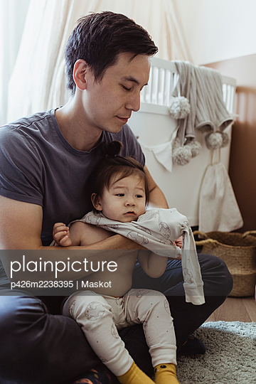 Father changing clothes of baby son at home - p426m2238395 by Maskot