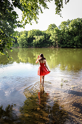 Woman in red dress standing in river - p1019m2099994 by Stephen Carroll