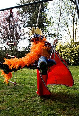 Boy on a swing dressed like a king  - p1231m1050930 by Iris Loonen