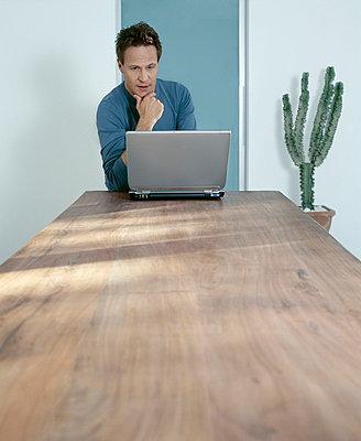 Mann mit Laptop am Tisch - p2685405 von icon art