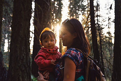 Mother holding a little girl in the forest at sunset in Sequoia National Park, California, USA - p300m2140319 by Gemma Ferrando