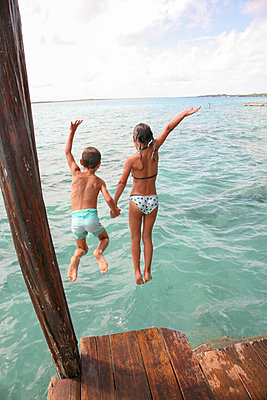 Children jumping into water - p375m1563864 by whatapicture