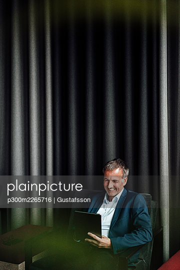 Happy senior businessman using digital tablet while sitting on chair against curtain in office cafeteria - p300m2265716 by Gustafsson