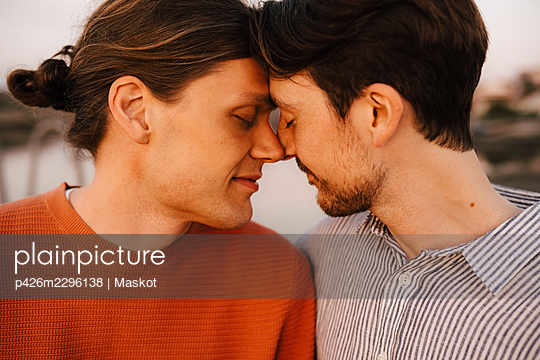 Romantic male friends touching forehead at evening - p426m2296138 by Maskot