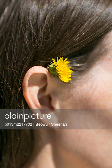 Woman with flower behind her ear - p919m2217702 by Beowulf Sheehan