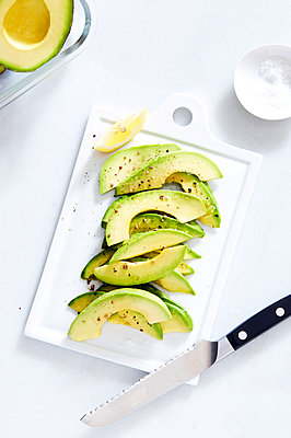 High angle view of avocado slices on cutting board over white background - p1166m1489959 by Cavan Images