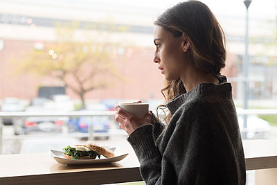 Side view of thoughtful woman having coffee - p1315m1484182 by Wavebreak