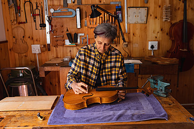 Female violin maker at work in a workshop - p1315m2131475 by Wavebreak