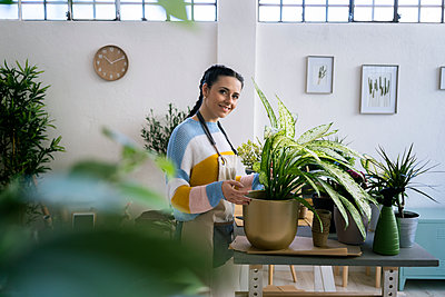 Young woman working in a gardening laboratory or plant shop - p300m2275341 von Giorgio Fochesato