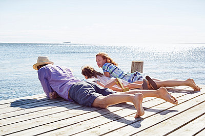 Family lying on pier;  Utvalnas;  Gavle;  Sweden - p429m860123f by Frank and Helena