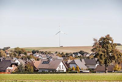 Dorf und Windturbine im Hintergrund - p893m2021682 von Thomas Ebert