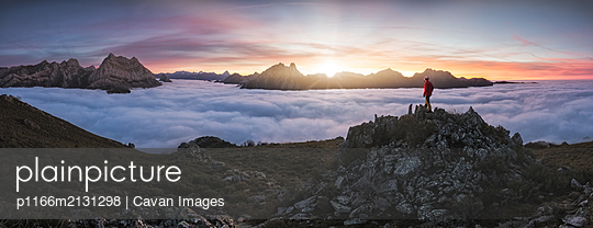 Man Observe Mists at sunrise from the top of some mountains - p1166m2131298 by Cavan Images