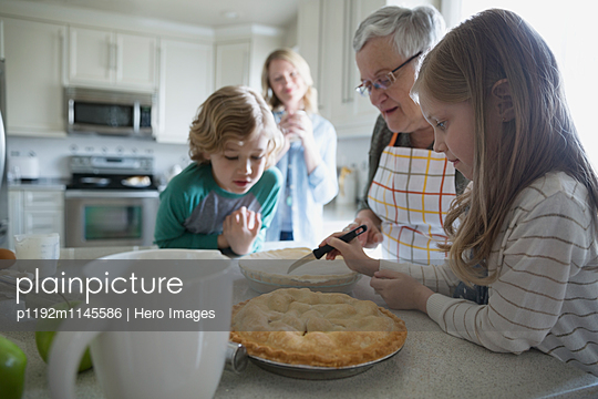 Multi-generation family baking homemade pies - p1192m1145586 by Hero Images