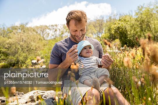 Vater und Baby am Seeufer - p1355m1574032 von Tomasrodriguez