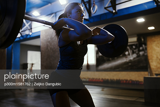 Woman lifting barbell in gym - p300m1581762 von Zeljko Dangubic