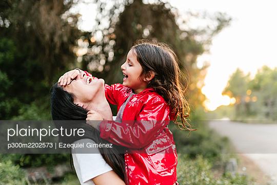 Mother holding her daughter outdoors - p300m2202573 by Ezequiel Giménez