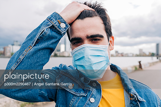 Man with hand in hair standing by sea during pandemic - p300m2290467 by Angel Santana Garcia