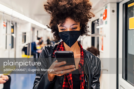Woman with face mask using mobile phone in subway train - p300m2290647 by Eugenio Marongiu