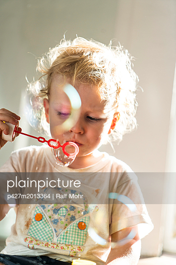Child blowing bubbles - p427m2013364 by R. Mohr