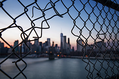 One World Trade Center seen through broken chainlink fence during sunset - p1166m1150610 by Cavan Images