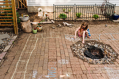 Little girl in arm cast draws on patio in backyard with sidewalk chalk - p1166m2106893 by Cavan Images