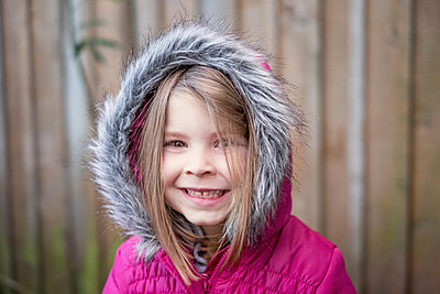 Young girl wearing pink fur hooded jacket - p1166m2200159 by Cavan Images