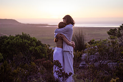 Teenage couple embracing at twilight - p1640m2245872 by Holly & John