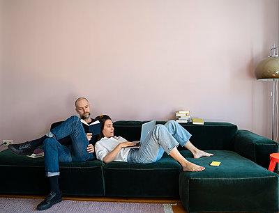 Paar mit Buch und Laptop auf dem Sofa - p432m2176104 von mia takahara