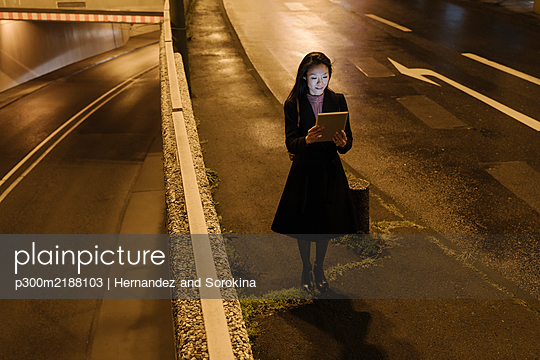 Young woman using tablet in the city at night, Frankfurt, Germany - p300m2188103 by Hernandez and Sorokina