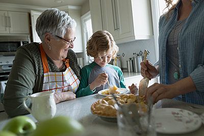 Multi-generation family eating homemade pie in kitchen - p1192m1145597 by Hero Images