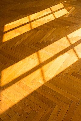 Shadow and light on herringbone parquet flooring - p300m1449621 by Christina Falkenberg