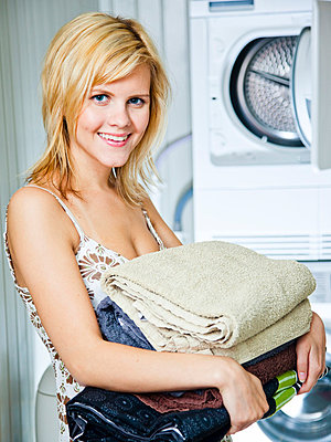 Woman with folded laundry - p4130625 by Tuomas Marttila