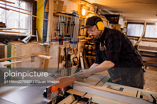 Carpenter in protective earmuffs working on machine - p1166m2279321 by Cavan Images