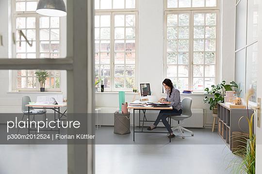 Woman working at desk in a loft office - p300m2012524 von Florian Küttler