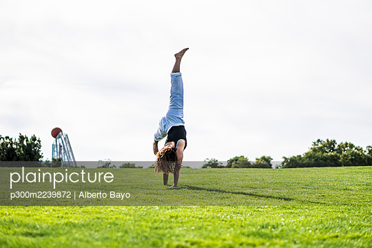Young woman practicing cartwheel on grass against clear sky - p300m2239872 by Alberto Bayo