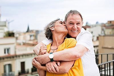 Romantic mature woman kissing senior man on terrace - p1166m1154302 by Cavan Images