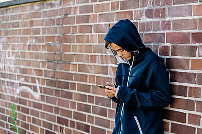 Teenager using his mobile standing on the  street.Brick wall - p1166m2137439 by Cavan Images