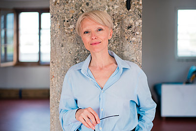 Smiling businesswoman standing against column at home - p300m2266958 by Robijn Page