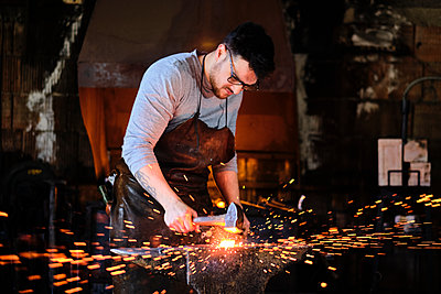 Young male blacksmith wearing eyeglasses forging with hammer at workshop - p300m2281500 by Antonio Ovejero Diaz