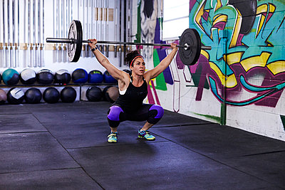 A female athlete trains in a crossfit gym.  - p343m1184148 by Josh Campbell