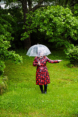Sweden, Dalarna, Woman wearing spotted raincoat standing in field - p352m1061638f by Lena Katarina Johansson