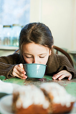 Young girl drinking hot drink - p9242966f by Image Source