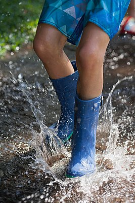 Boy in wellies splashing in puddle of water - p924m1125640f by Kinzie Riehm