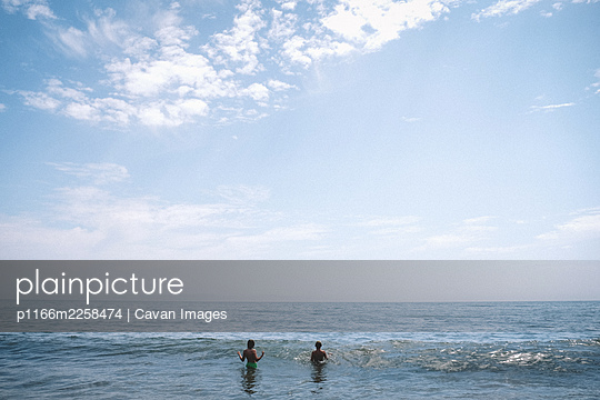 Two Small Figures Head out into a Vast Ocean - p1166m2258474 by Cavan Images