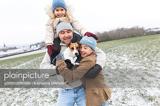 Happy father with two children and dog in winter landscape - p300m2080986 by Katharina Mikhrin
