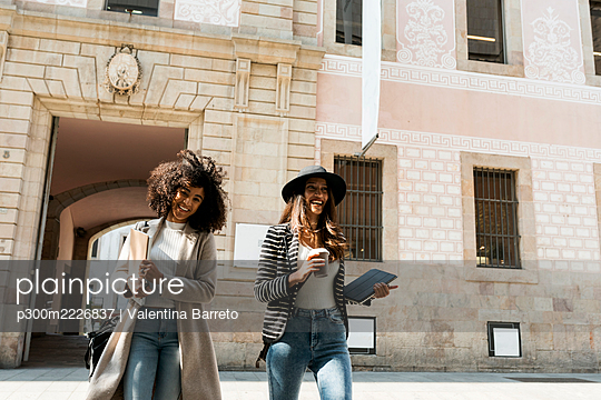 Smiling female coworkers walking on street against building in city - p300m2226837 by Valentina Barreto