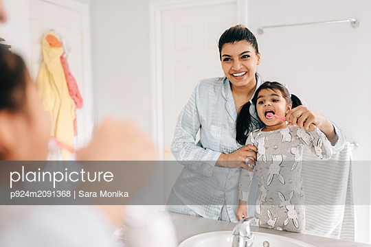 Girl with mother brushing her teeth in bathroom mirror, over shoulder view - p924m2091368 by Sara Monika